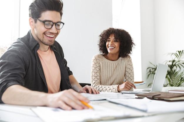 Счастливые молодые коллеги читают документы, сидя за столом в офисе