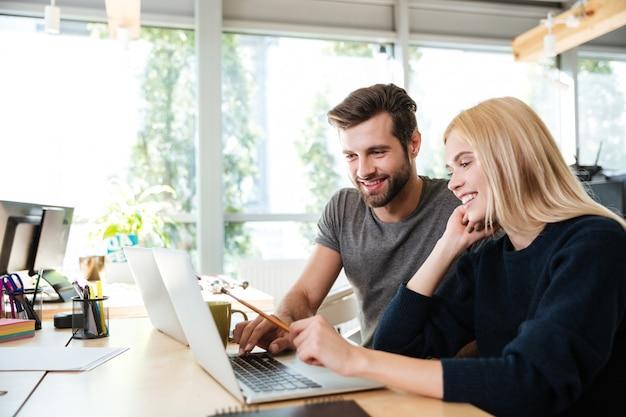 Счастливые молодые коллеги, сидя в офисе коворкинг, используя ноутбук