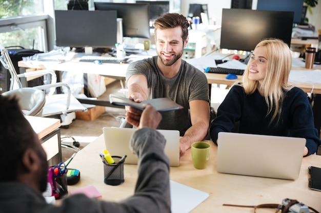 オフィスのコワーキングに座っている幸せな若い同僚