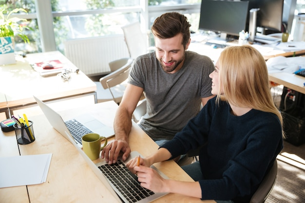 Happy young colleagues sitting in office coworking using laptop