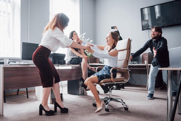 幸せな若い同僚が笑顔でクリエイティブオフィスで楽しんでいます。