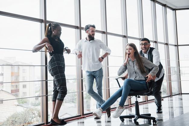 행복한 젊은 동료들은 미소를 짓고 창의적인 사무실에서 즐거운 시간을 보냅니다.