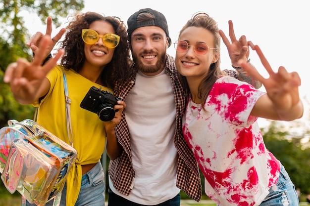 Felice giovane compagnia di amici sorridenti emotivi che camminano nel parco con macchina fotografica, uomini e donne che si divertono insieme