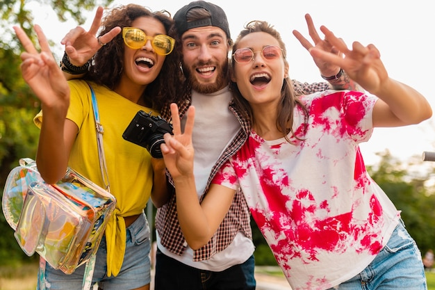 Happy young company of emotional smiling friends walking in park with photo camera, man and women having fun together
