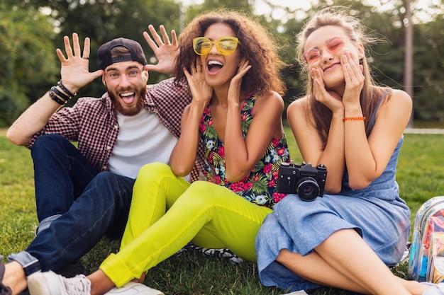 Felice giovane compagnia di amici seduti nel parco scherzare con facce buffe pazze, uomini e donne che si divertono insieme, viaggiando con la macchina fotografica