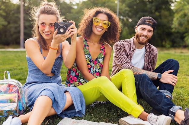 Felice giovane compagnia di amici seduti al parco, uomini e donne che si divertono insieme, che viaggiano prendendo foto sulla fotocamera, parlando, sorridendo