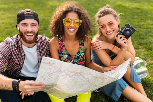 Happy young company of friends sitting park traveling looking in map sightseeing, man and women having fun together,
