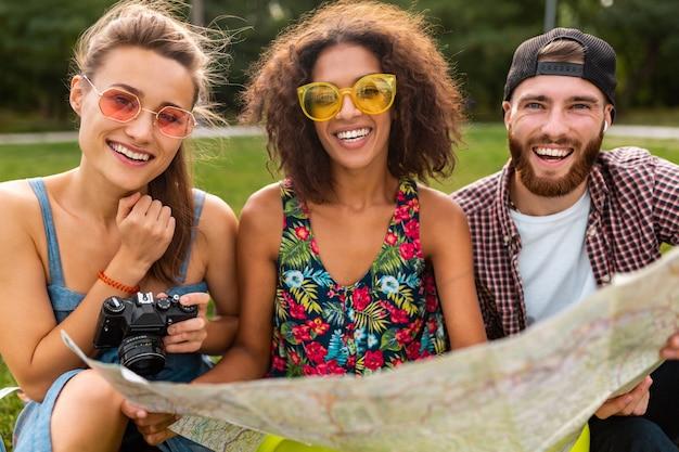 Felice giovane compagnia di amici seduti nel parco che viaggiano guardando nella mappa visite turistiche, uomini e donne che si divertono insieme