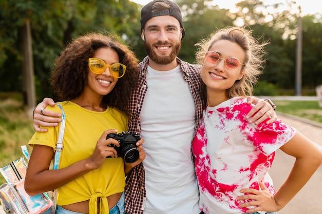 一緒に楽しんでいる写真カメラ、男性と女性と一緒に公園を歩いている感情的な笑顔の友人の幸せな若い会社