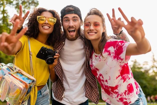Счастливая молодая компания эмоционально улыбающихся друзей, гуляющих в парке с фотоаппаратом, мужчины и женщины, весело проводящие время вместе