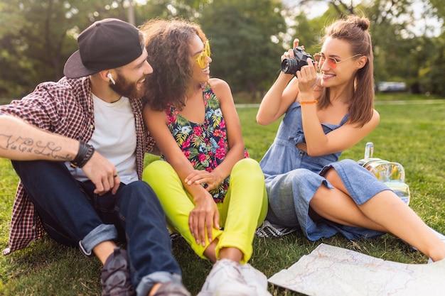 公園に座っている友人の幸せな若い会社、一緒に楽しんでいる男性と女性、カラフルな夏の流行に敏感なファッションスタイル、カメラで旅行、率直に笑う