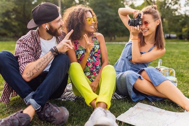 公園に座っている友人の幸せな若い会社、一緒に楽しんでいる男性と女性、カラフルな夏の流行に敏感なファッションスタイル、カメラで旅行、写真を撮る
