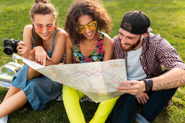 地図の観光、男性と女性が一緒に楽しんで探して公園旅行に座っている友人の幸せな若い会社