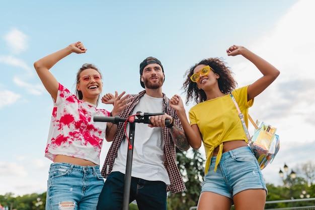 Счастливая молодая компания улыбающихся друзей, танцующих, гуляющих по улице с электрическим самокатом, мужчины и женщины, весело проводящие время вместе