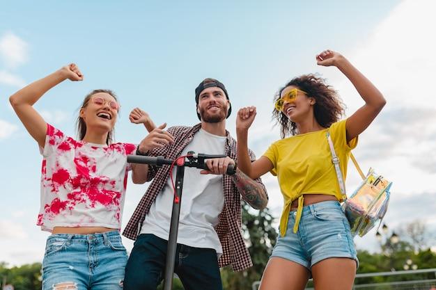 電動キックスクーター、男性と女性が一緒に楽しんで通りを歩いて踊る笑顔の友人の幸せな若い会社