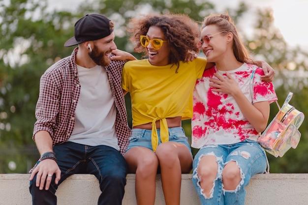 Счастливая молодая компания улыбающихся друзей, сидящих в парке, мужчины и женщины, весело проводящие время вместе