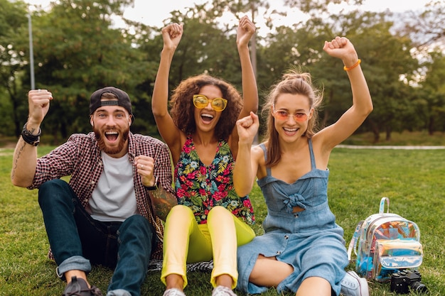 Счастливая молодая компания улыбающихся друзей, сидящих в парке на траве, мужчины и женщины, весело проводящие время вместе