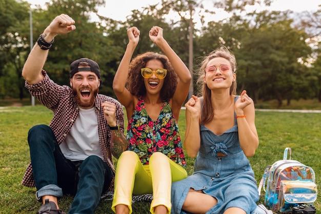 草の上に公園に座っている笑顔の友人、一緒に楽しんでいる男性と女性の幸せな若い会社