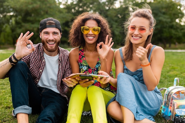 스마트 폰을 사용하여 공원에 앉아 웃는 친구의 행복한 젊은 회사, 함께 재미 다채로운 여름 스타일, 통신 무선 연결 장치, 카메라에서 긍정적 인 찾고