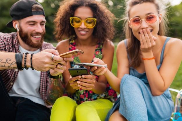 스마트 폰, 남자와 여자가 함께 재미를 사용하여 공원에 앉아 웃는 친구의 행복 젊은 회사
