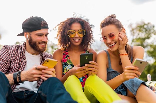 Счастливая молодая компания улыбающихся друзей, сидящих в парке, используя смартфоны, мужчины и женщины, весело проводящие время вместе