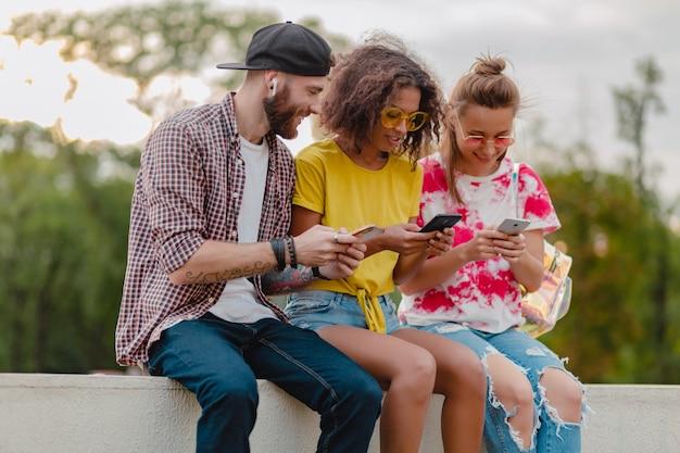 スマートフォンを使用して公園に座っている笑顔の友人、楽しんでいる男性と女性の幸せな若い会社