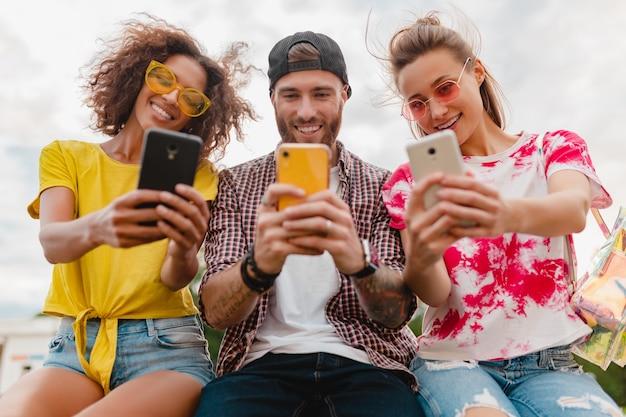 スマートフォンを使用して公園に座っている笑顔の友人の幸せな若い会社