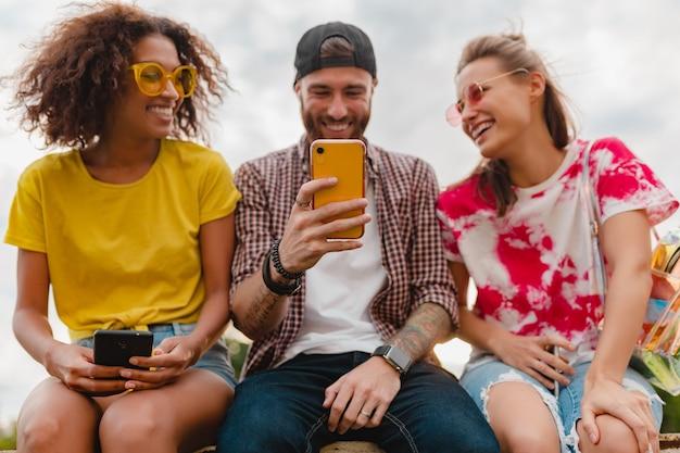 Счастливая молодая компания улыбающихся друзей, сидящих в парке с помощью смартфонов