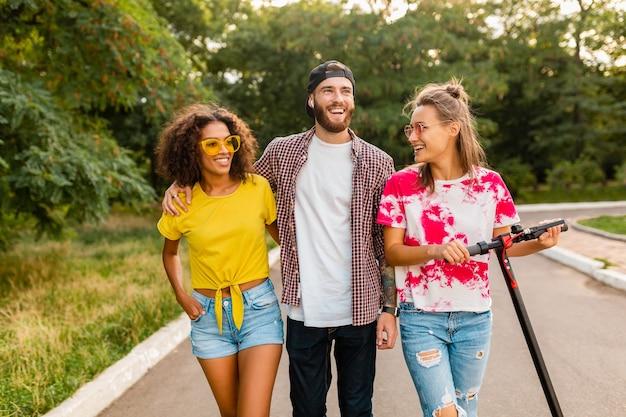 電動キックスクーター、男性と女性が一緒に楽しんで公園を歩いている笑顔の友人の幸せな若い会社
