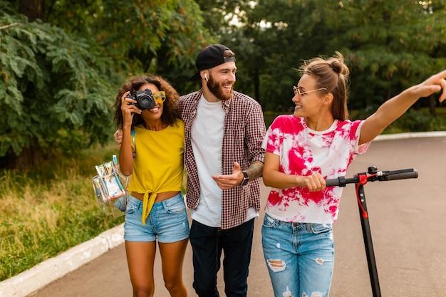 Счастливая молодая компания улыбающихся друзей, гуляющих в парке с электрическим самокатом, мужчины и женщины, весело проводящие время вместе