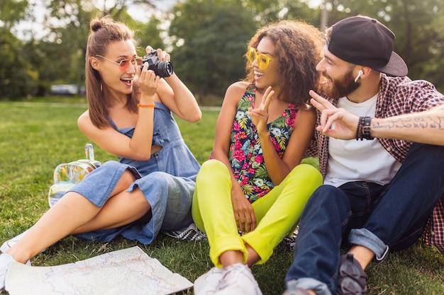 公園に座っている笑顔の友人、一緒に楽しんでいる男性と女性、カラフルな夏の流行に敏感なファッションスタイル、カメラと一緒に旅行の話の幸せな若い会社