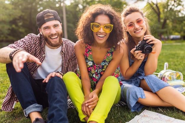 公園に座って、カメラと一緒に旅行して、一緒に楽しんでいる男性と女性の笑顔の友人を話す幸せな若い会社