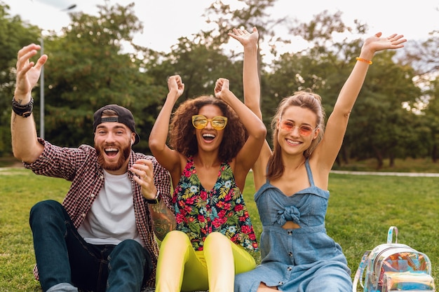 Happy young company of smiling friends sitting park on grass, man and women having fun together
