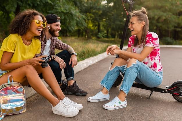Felice giovane compagnia di amici sorridenti seduti nel parco sull'erba con scooter elettrico, uomini e donne che si divertono insieme