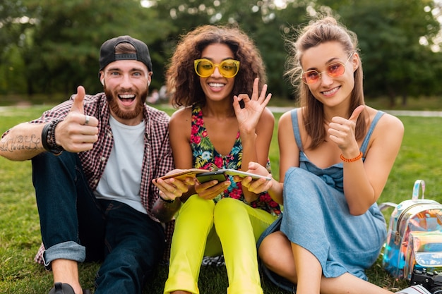 Felice giovane compagnia di amici sorridenti seduti al parco utilizzando smartphone, divertirsi insieme in stile estivo colorato, dispositivi di connessione wireless di comunicazione, guardando positivo nella fotocamera