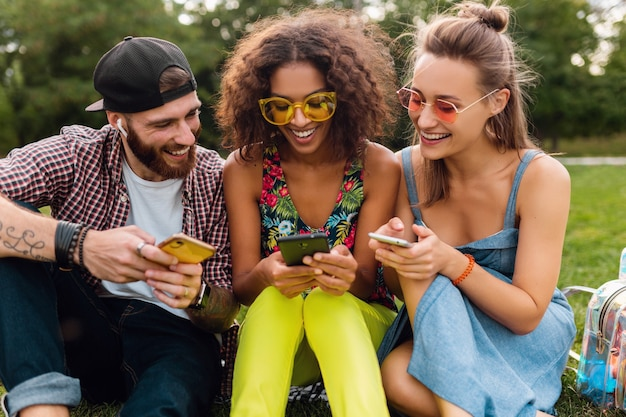 Felice giovane compagnia di amici sorridenti seduti nel parco utilizzando smartphone, uomini e donne che hanno divertimento insieme