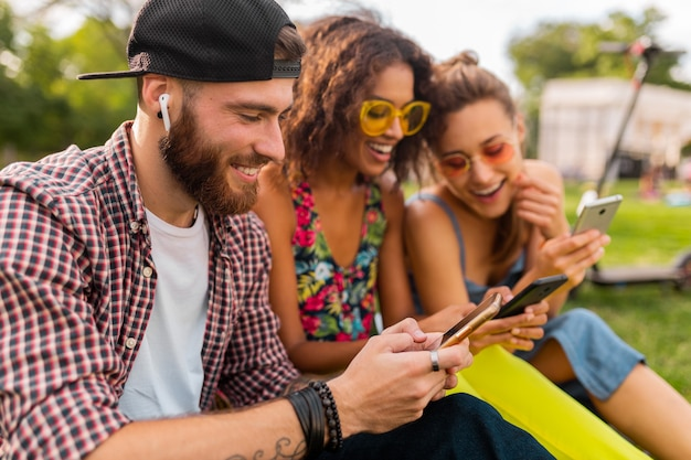 Happy young company of smiling friends sitting park using smartphones, man and women having fun together