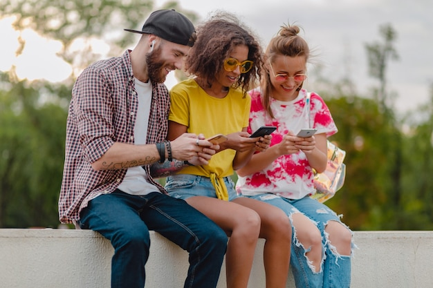 Happy young company of smiling friends sitting park using smartphones, man and women having fun