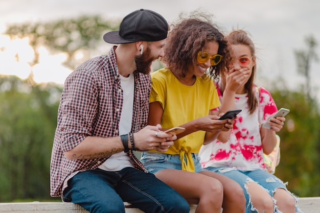 Felice giovane compagnia di amici sorridenti seduti nel parco utilizzando smartphone, uomo e donna divertendosi