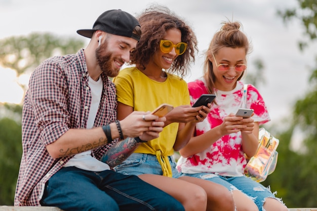 Happy young company of smiling friends sitting park using smartphones