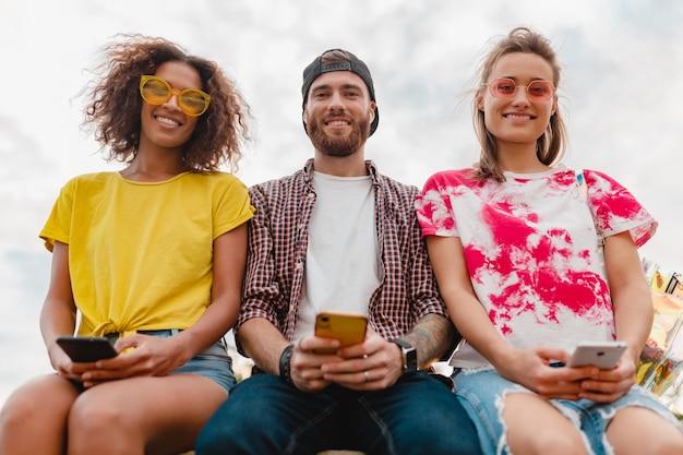 Felice giovane compagnia di amici sorridenti seduti nel parco utilizzando gli smartphone