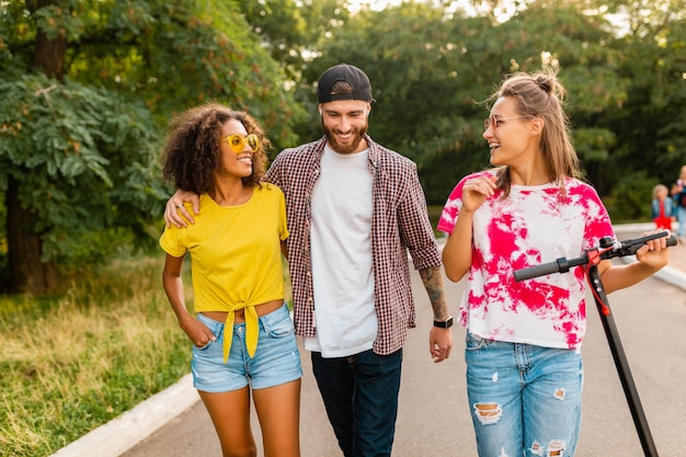 Happy young company of smiling friends walking in park with electric kick scooter, man and women having fun together