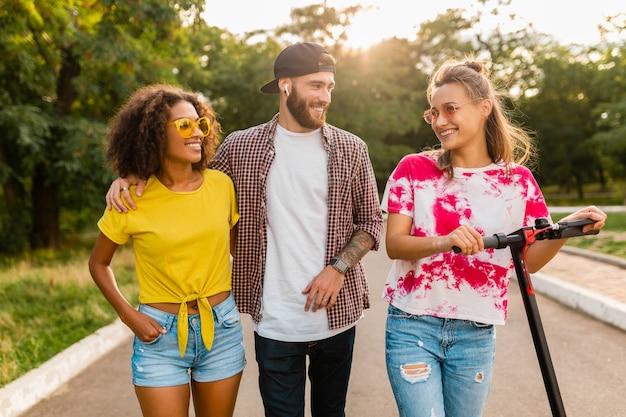 Felice giovane compagnia di amici sorridenti che camminano nel parco con scooter elettrico, uomini e donne che si divertono insieme