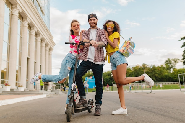 Happy young company of smiling friends walking in street with electric kick scooter, man and women having fun together