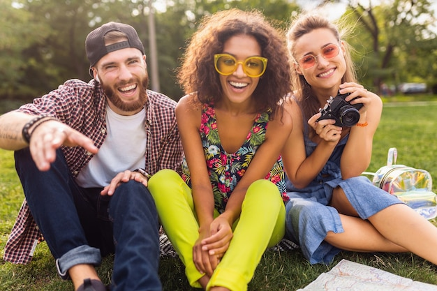 Happy young company of talking smiling friends sitting park, man and women having fun together, traveling with camera