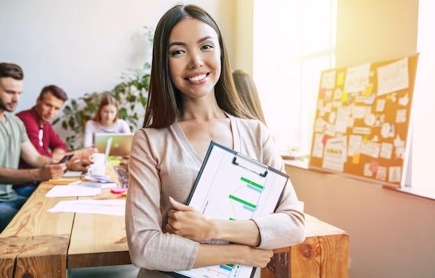 スマートカジュアルウェアの幸せな若い自信を持って美しいアジアのビジネス女性は、現代のビジネスチームの背景にポーズをとっています。同僚。チームを立ち上げます。一緒に学生