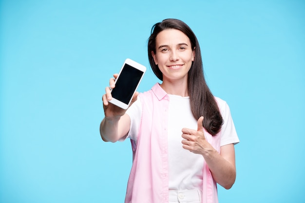 Счастливый молодой потребитель показывает палец вверх и представляет вам промо или рекламу на своем смартфоне