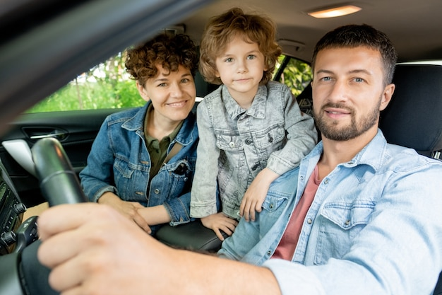Happy young contemporary family of three in denim jackets looking at you with smiles while sitting in the car and going to countryside