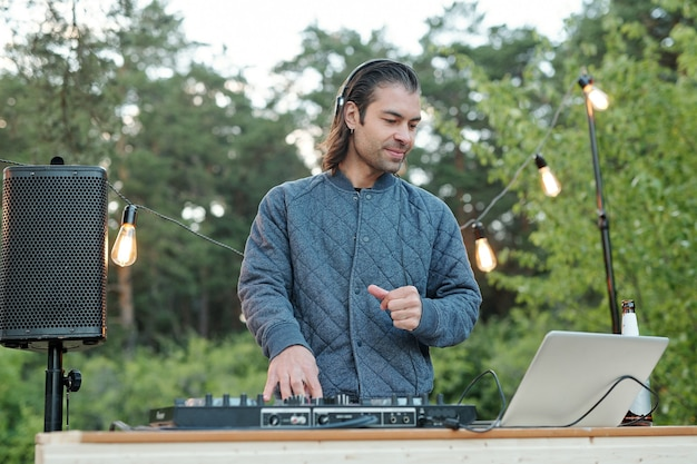 자연 환경에서 스테레오 보드의 사운드를 조정하는 동안 노트북 디스플레이를보고 헤드폰에 행복 젊은 현대 남자