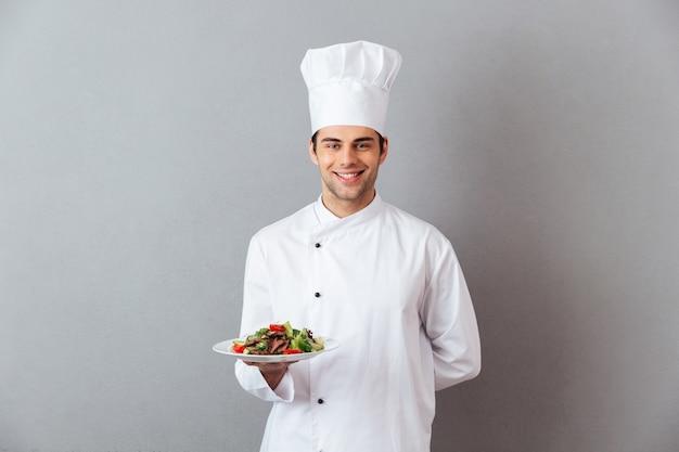 Счастливый молодой повар в форме проведения салата.